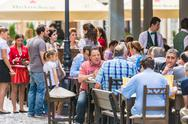 Stock Photo of Tourists Having Lunch At Outdoor Restaurant