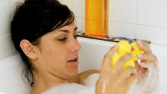 Girl playing in bath tub with two little yellow duck Stock Footage