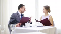 Smiling couple with menus at restaurant Stock Footage