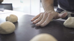 Hand kneading across bread dough in a black countertop in profile - stock footage