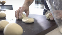 Man kneading 2 piles of bread dough in black countertop - stock footage