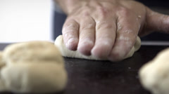 Hand kneading forward and backward bread dough in a black countertop in front Stock Footage