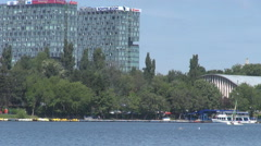 Business tower view glass buildings, boat moving on lake slowly, green landscape - stock footage