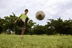Kid playing football and soccer game in park Kuvituskuvat