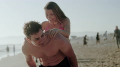 Man gives girl piggyback ride on beach in 4K Stock Footage