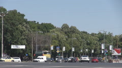Car traffic on boulevard, tourism bus, green trees besides, natural background Stock Footage