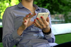 Businesswoman hands texting on smartphone in the park NTSC Stock Footage