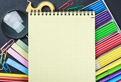 school stationery laid out on the notepad - stock photo
