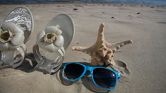 Sunglasses flip flops and starfish on beach. HD with motorized slider. 1080p. Stock Footage