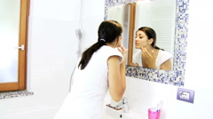 Young woman checking skin and pimples on mirror in bathroom Stock Footage