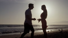 Man Proposes to Woman Sunset-lit beach Ocean Shore Evening Romantic Love 4K Stock Footage