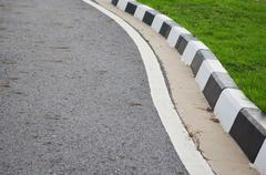 Road and footpath with grass. Stock Photos