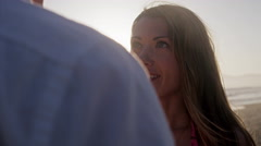 Beautiful woman looking up at boyfriend on sunset-lit beach in 4K Stock Footage