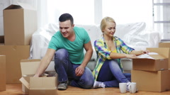 Smiling couple unpacking boxes with kitchenware Stock Footage