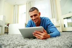 Happy lying on the carpet and using tablet computer at home Stock Photos
