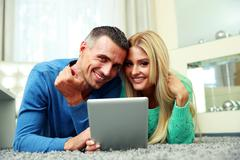 smiling couple lying on the carpet and using tablet computer together - stock photo