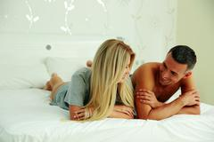happy couple lying on the bed and looking at each other - stock photo