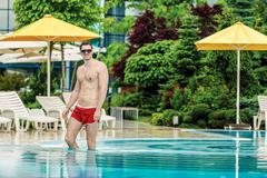 Young healthy good looking macho man model athlete at hotel outdoor pool Stock Photos