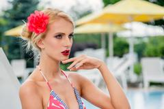 Sexy and stylish portrait of a woman in swimsuit on a spa resort in the pool  Stock Photos