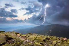 Ukkosta vaaleneminen ja dramaattisia pilviä vuorilla Kuvituskuvat
