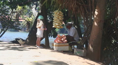 Man selling popcorn on the street by the lake and talking with a little girl. Stock Footage