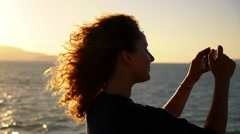 Profile of Happy Smiling Woman Using Phone Camera against Beautiful Sunrise. Stock Footage