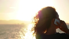 Young Woman Talking by iPhone on the Ship against Beautiful sunset - stock footage