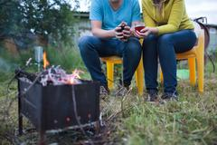 Couple with tea cups in hands near the smouldering fire Stock Photos