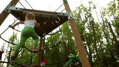 Cute little girl climbing on a Jungle Gym rope game - stock footage