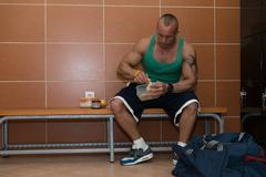 bodybuilder eating healthy diet food out of tupperware - stock photo