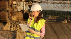 Ingineer thinking in front of huge excavator Stock Footage