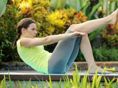Young woman doing sit-ups in the garden NTSC Stock Footage