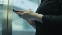 Woman is Using Mobile Phone in Elevator Stock Footage
