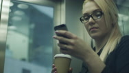 Stock Video Footage of Woman Drinking Coffee and Using Mobile Phone in Elevator