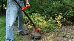Closeup of man using garden Weed Trimmer 1 HD Stock Footage