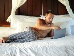 Young man with laptop relaxing on comfortable bed NTSC Stock Footage