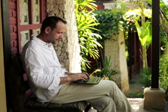 Young man sitting with laptop on bench in front of country house NTSC Stock Footage