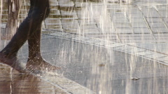 Girl playing in cool water fountain on a hot summer day - stock footage