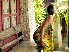 Young, beautiful woman relaxing on bench in front of country house NTSC Stock Footage