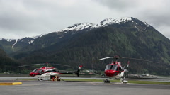 Two helicopters parking on airstrip - Alaska, snowy mountains background Stock Footage