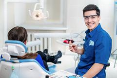 Healthy teeth! smiling dentist holding a drill in his hands and treats teeth Kuvituskuvat
