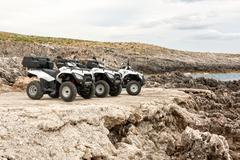 Quad bikes at a rough terrain Stock Photos