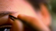 Part of face woman plucking eyebrows depilating with tweezers. Macro video Stock Footage