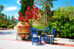 the amphora with flowers and traditional greek table and chairs at luxury hot - stock photo