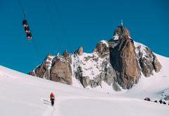 the aiguille du midi peak with panoramic mont-blanc cable car; in foreground - stock photo