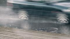 Cars drive on wet asphalt near the sidewalk, rainy weather, street close-up Stock Footage