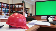Stock Video Footage of Engineer work place with green chromakey screen pc and hardhat on table