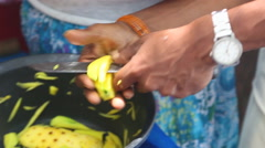 Woman vendor slicing mangos for selling on her stand in Kandy, Sri Lanka Stock Footage