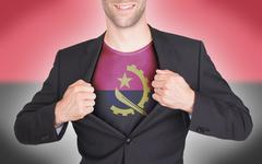 Businessman opening suit to reveal shirt with Angola flag Stock Photos