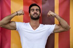 Attractive bold young man showing biceps Stock Photos
